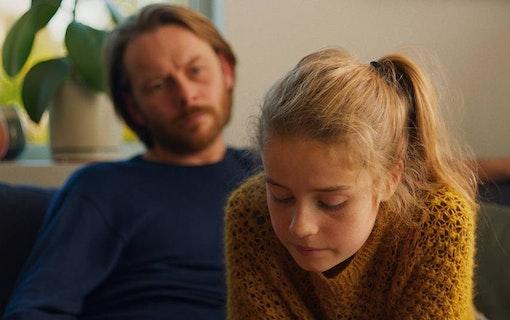 Bild från den norska filmen Barn föreställandes flickan Lykke i förgrunden och läraren Anders i bakgrunden.