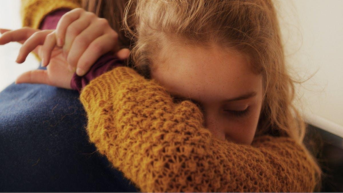 Bild från den norska filmen Barn föreställandes en flickan Lykke kramades läraren Anders.