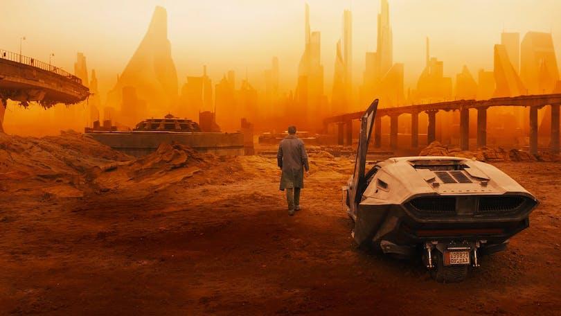 En blade runner och hans bil i ett ökenlandskap i Blade Runner 2049.