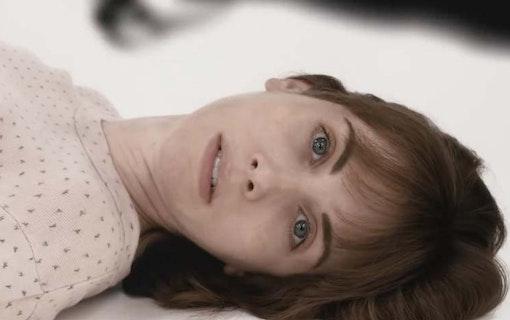 """Huvudkaraktären i """"Horse Girl"""" ligger på ett vitt golv och tittar in i kameran."""