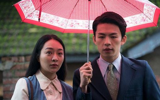 En ung kvinna och en ung man står under ett paraply i finkläder.