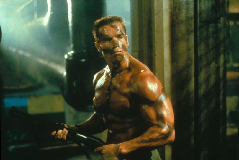En välpumpad och barbröstad Arnold Schwarzenegger gör sig redo för slutstriden i Commando. Foto: 20th Century Fox.