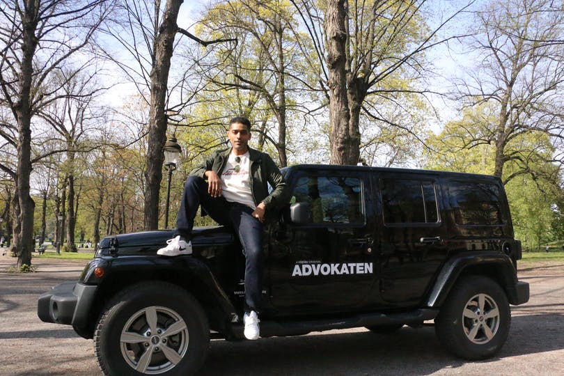 Alexander Karim sittandes på sin Advokaten-bil.