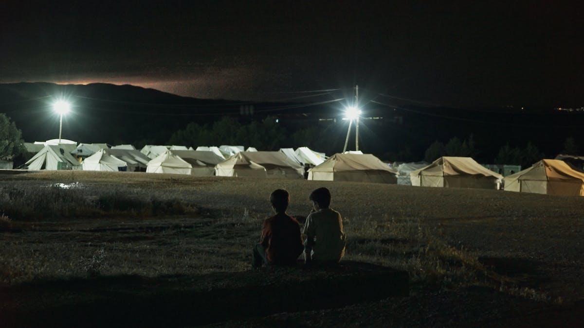 Två pojkar umgås utanför ett flyktingläger