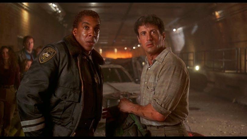 Stallone får det hett om öronen och kallt om tårna i en tunnel som långsamt fylls med vatten och hans frambrölade repliker. Foto: Universal Pictures.