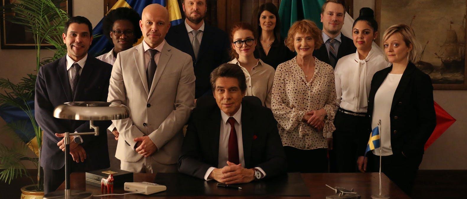 En bild på rollbesättningen i Viaplay-serien Ambassadören, med Mikael Tornving i mitten.