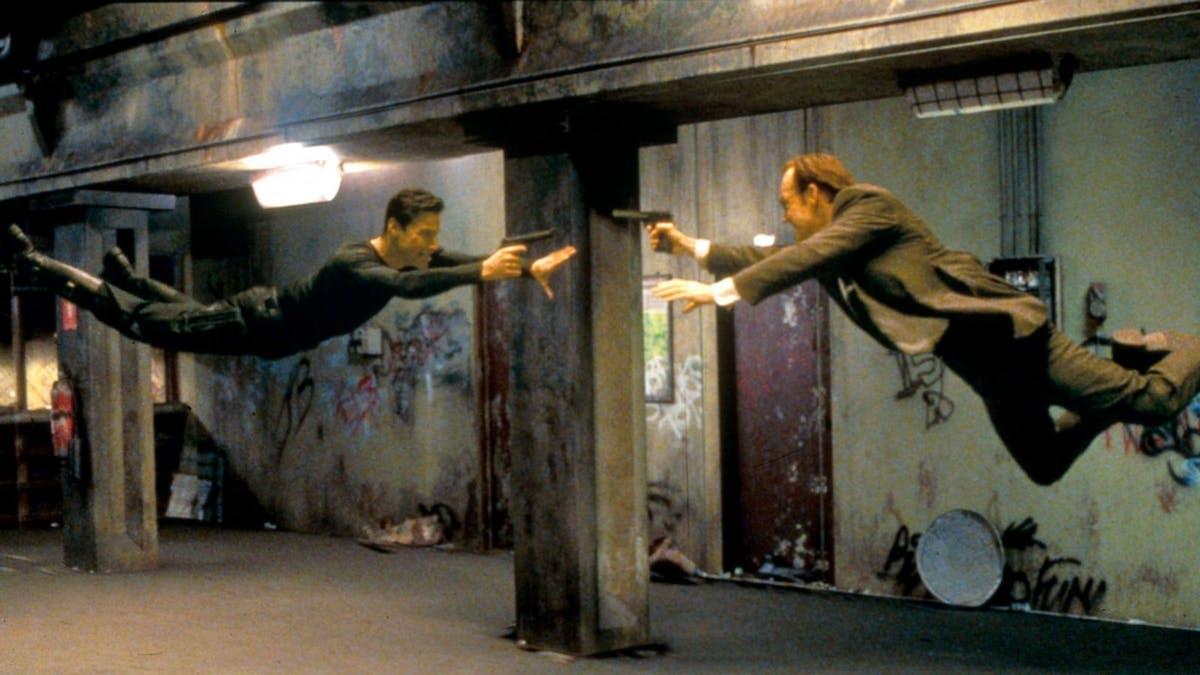 Neo (Keanu Reeves) och Agent Smith hoppar mot varandra med pistoler i händerna. Foto: Warner Bros. Pictures.