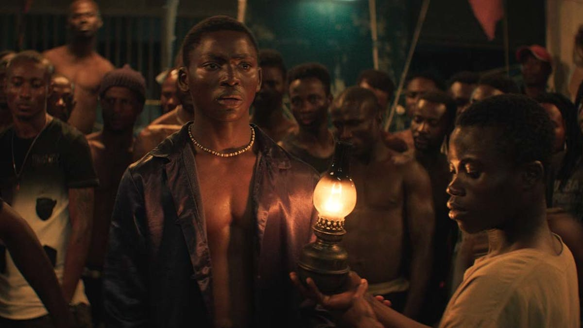 Mitt i bilden står skådespelaren Bakary Koné  i rollen som berättaren Roman i filmen Night of the Kings. Bakom honom ett antal fångars som lyssnar. Foto: Banshee Films