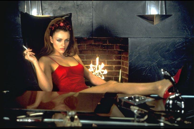 Elizabeth Hurley med ena benet på ett skrivbord