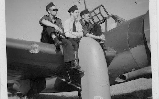 Svartvit bild på en ung Anders Rogberg och ett par andra piloter som sitter på vingen på ett stridsflygplan. Foto: Lightray Productions.